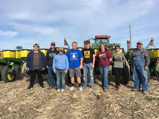 Photo of Alex Cox, Joe Tonelli, Ethan Pegump, Tyler Steines, Bryce Mougin, Delaney Bulechek, Kathe Nelson, and Farmer Gene Charbon